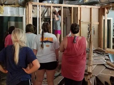 Team members help construct a home
