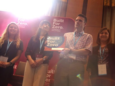 Team member holding up Built for Zero signage on stage at a conference