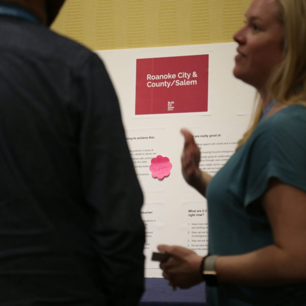 Woman gesturing in front of a poster at conference