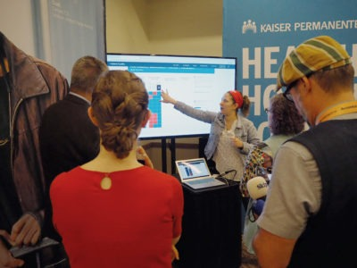 Person pointing to graph on screen in front of small crowd