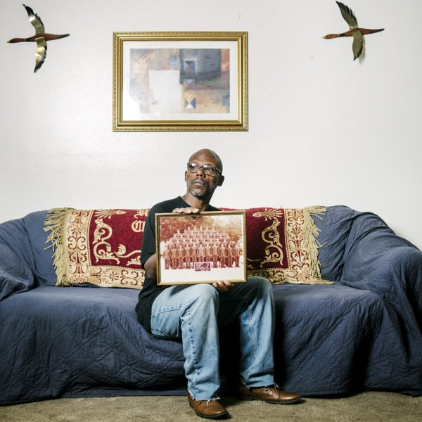 Man sitting on couch holding photo