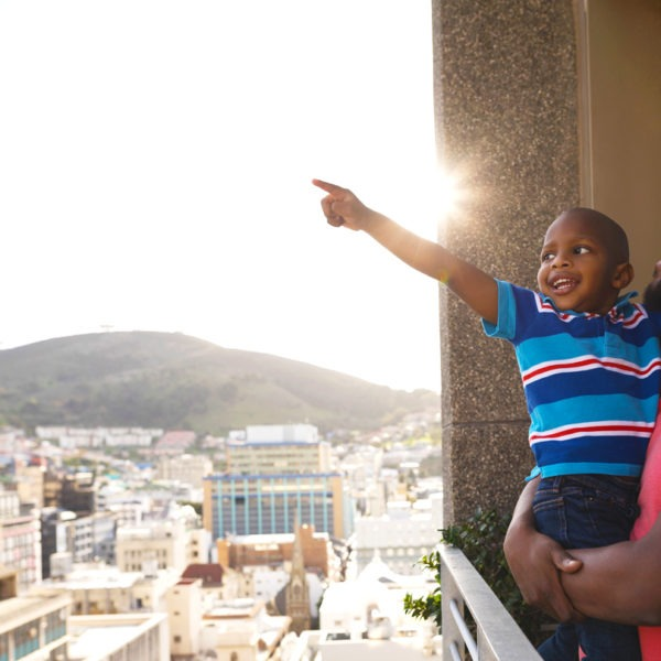 Man holding child on balcony while both smile and child points