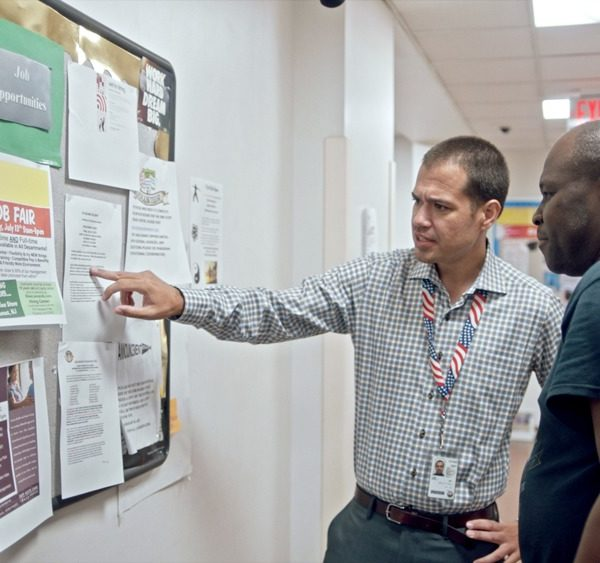 Two men looking at bulletin board with papers