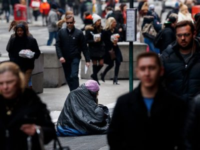 People on busy street around person experiencing homelessness