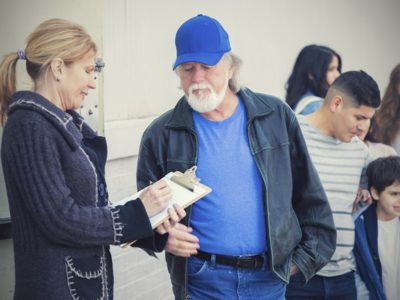 Woman with clipboard talking with older man in line