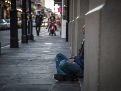 Person sitting on the ground on a street
