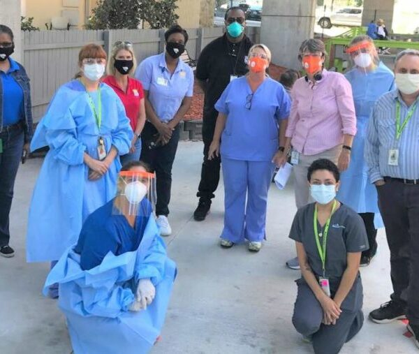 Group of people in scrubs, masks, and PPE