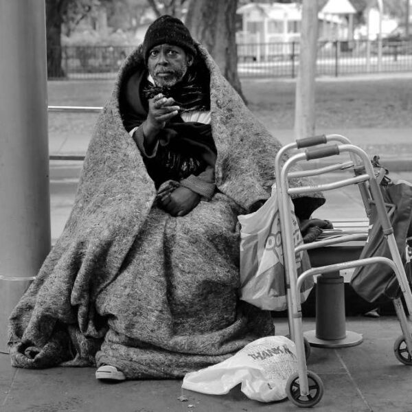 Man on park bench with blanket and walker