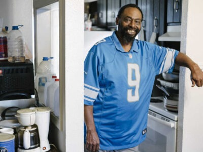 Man smiling in an apartment kitchen